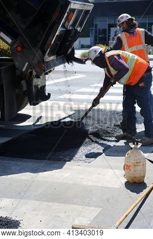Long Beach, California USA - March 15, 2021: Workers with Asphalting machine during Road street repair work. Street resurfacing. Fresh asphalt construction. Work Men filling Pot Holes. Editorial.