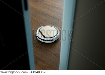 Photo Of A Robot Vacuum Cleaner In The Opening Working On The Floor In The Apartment