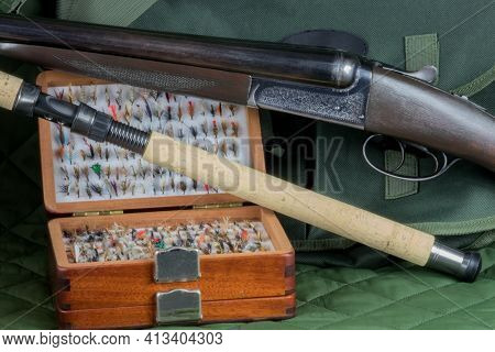 Old Shotgun With Fishing Rod And Fly Box And Game Bag On An Outdoor Coat