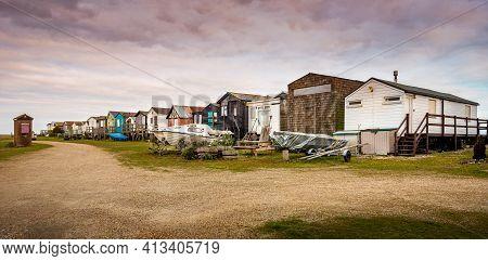 Seasalter, Kent, England - Mar 7 2021: Close Up Rear View Of Beach Huts And Boats At Sunrise At Seas