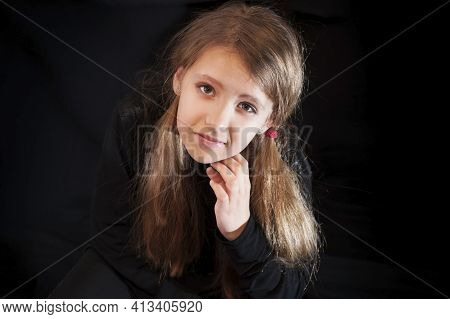 Portrait Of A Young Girl On A Black Background. She Has A Sad Face And A Conceived Look