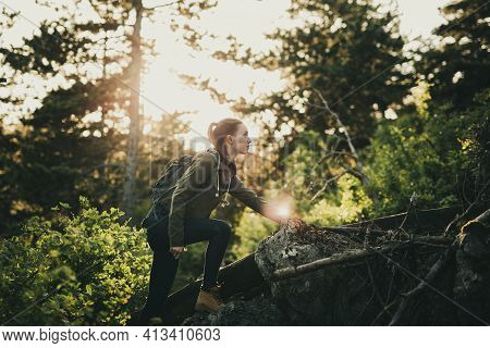 Beautiful Young Girl, In Outdoor Clothing With Camelbag, Climbing On Raised Rock In Middle Of Wilder