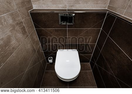 Ceramic Toilet Bowl With Toilet Seat, Chrome Wall Button And Toilet Brush In Restroom. Paving And Ti