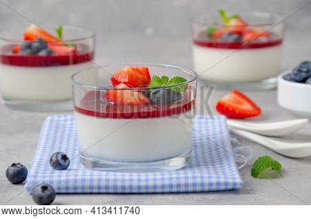 Italian Dessert Panna Cotta In A Glass With Berry Sauce, Fresh Strawberries And Blueberries On Top O