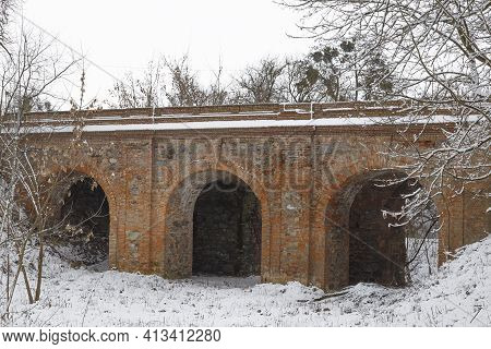 Arched Stone Bridge Leading To The Ruins Of  Old Abandoned Korets Castle In The Snow.  Koretsk City.