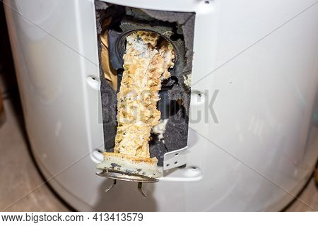 Repair And Maintenance Of Boilers. A Tubular Electric Heater Covered With Lime Scale Sticks Out Of T