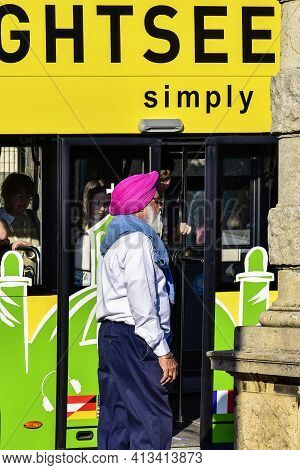 Austria, Vienna - May 2019: An Elderly Indian Man Near A Tourist Atvobus. Tourists In The Historical
