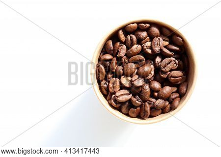 Roasted Coffee Beans In A Kraft Paper Cup. Top View, Copy Space