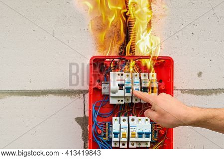 Finger Of Male Hand Turns Off Burning Switchboard From Overload Or Short Circuit On Wall Closeup. Ci