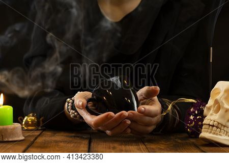 Fortune Teller Or Oracle With Holding A Black Cup For Fortune Telling On The Coffee Grounds. Psychic