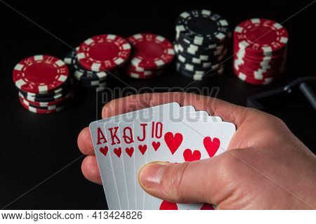 Poker Cards With A Royal Flush Combination. Close-up Of A Gambler Hand Is Holding Playing Cards In C