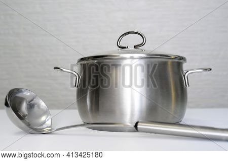 Stainless Steel Pot, Stockpot And A Ladle On White Table, Eco Friendly Kitchen Utensils Without Harm
