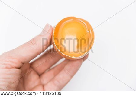 A Hand Holding Half Broken Egg With Yellow Yolk In A Shell Against White Background Close Up