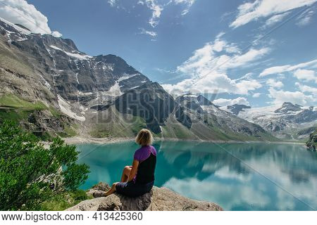 Girl Sitting And Enjoying Beautiful View Of Mountain Lake Near Kaprun,austria.quiet Relaxation Outdo