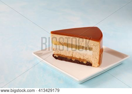 A Single Piece Of Mousse Cake In A Cut On A Plate On The Table