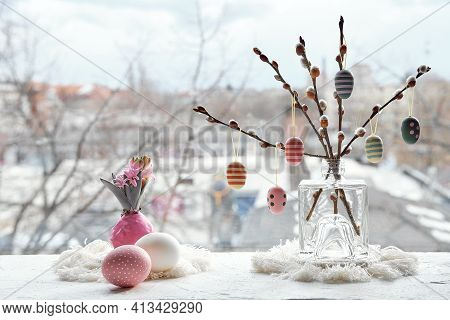 Easter Decorations On Window Sill In Spring. Wooden Painted Eggs On Pussy Willow Twigs In Glass Bott