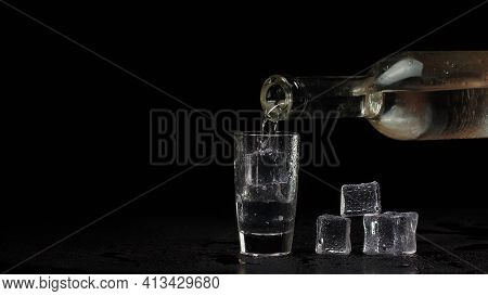 Bartender Pouring Up Shot Of Vodka With Ice Cubes From Bottle Into Drinking Glass Against Black Back