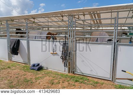 Temporary Stables For Horses With Equipment Hanging On Exterior,