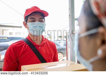 Asian Delivery Servicemen Wearing A Red Uniform With A Red Cap And Face Mask Handling Cardboard Boxe