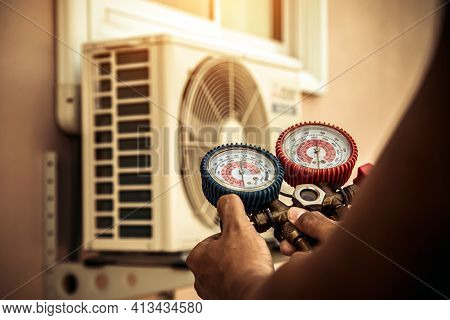 Air Repair Mechanic Using Measuring Manifold Gauge Equipment For Filling Home Air Conditioner After
