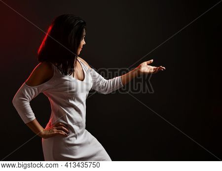 Beautiful Wise Adult Brunette Woman In White Stylish Dress Stands Side To Camera Talking And Activel