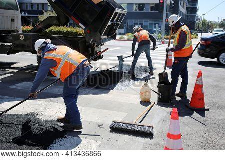 Long Beach, California USA - March 15, 2021: Workers with Asphalting machine during Road street repair work. Street resurfacing. Fresh asphalt construction. Work Men filling Pot Holes. Editorial.