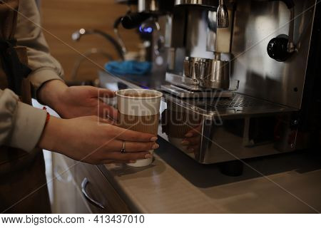 The Barista Prepares Coffee On A Professional Coffee Machine. Coffee In A Paper Glass In The Backgro