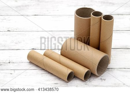 Cardboard Cylinders On A White Wooden Table