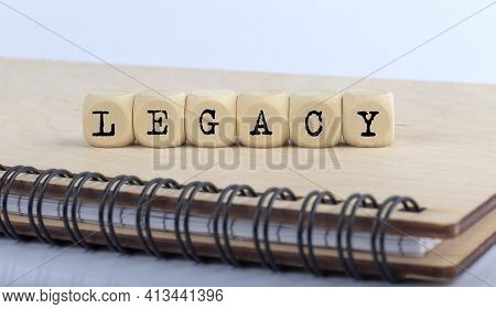 Word Legacy Made With Letters On Wooden Blocks On The Wooden Notepad