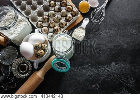 Ingredients For Baking Eggs, Flour, Milk And Utensils On A Black Background