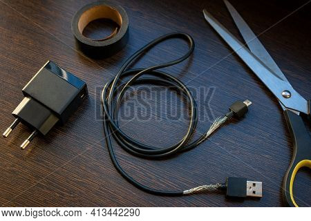 Old Mobile Charger Wire For Smartphone With Bare Wires And Electrical Tape Fix Concept