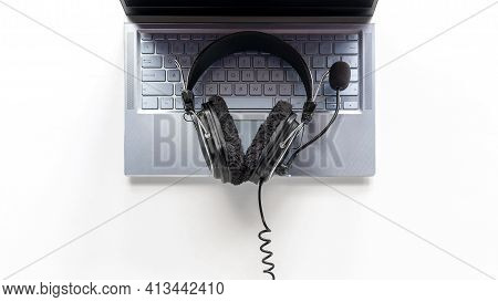 Laptop And Headphones With Microphone On White Background Concept Of Remote Work, Operator, Tech Sup
