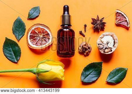 Perfume And Ingredients On Orange Background Close Up