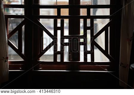 Wooden Banister Balcony Frame Decorating Near Glass Window. Architectural Decoration