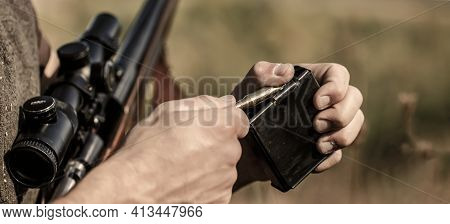 Man Is Charging A Hunting Rifle. Male Hunter In Ready To Hunt. Closeup. Ammunition With A Gun, Cartr