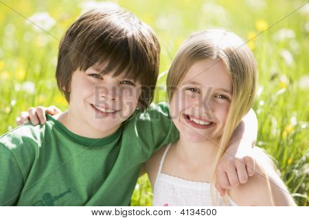 Two Young Children Sitting Outdoors Arm In Arm Smiling