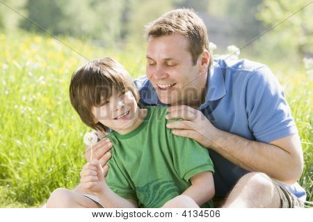 Father And Son Sitting Outdoors With Dandelion Head Smiling