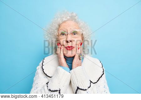 Beautiful Elderly Woman Keeps Hands On Face Folds Red Painted Lips Wears Spectacles White Jumper Has