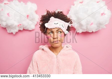 Photo Of Discontent Thoughtful Curly African American Woman Looks Pensively Aside Smirks Face Applie