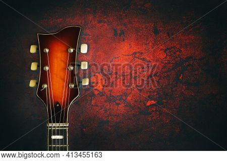 Neck, Of An Old, Jazz Electric Guitar, On A Red Grunge Background. Close-up. Copy Space. Background