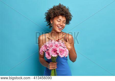 Happy Dark Skinned Pleased Woman Enjoys Romantic Date Gets Bouquet Of Gerbera Flowers From Boyfriend