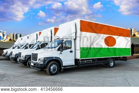Niger Flag On The Back Of Five New White Trucks Against The Backdrop Of The River And The City. Truc