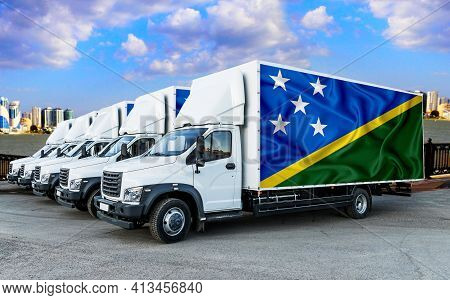 Solomon Islands Flag On The Back Of Five New White Trucks Against The Backdrop Of The River And The