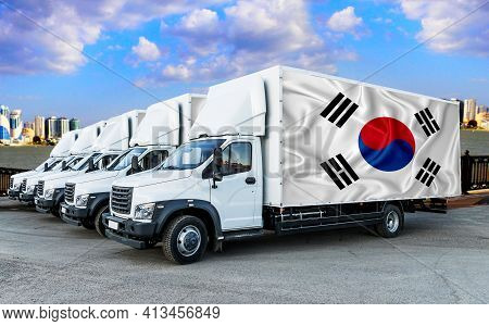 South Korean Flag On The Back Of Five New White Trucks Against The Backdrop Of The River And The Cit