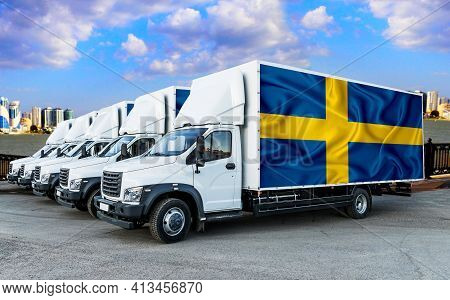 Sweden Flag On The Back Of Five New White Trucks Against The Backdrop Of The River And The City. Tru
