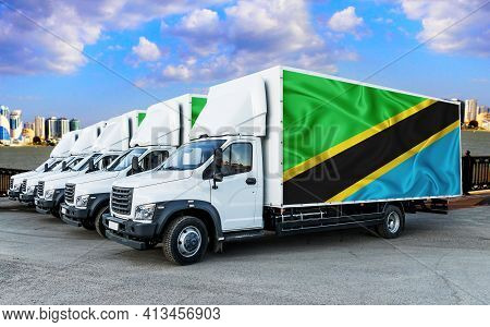 Tanzania Flag On The Back Of Five New White Trucks Against The Backdrop Of The River And The City. T