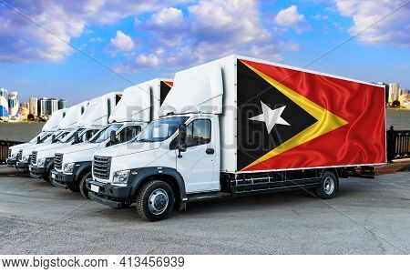 Timor Flag On The Back Of Five New White Trucks Against The Backdrop Of The River And The City. Truc