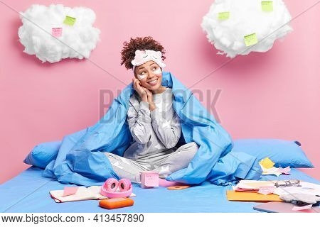 Pleased Young Afro American Dressed In Nightwear Looks Aside With Pensive Face Expression Applies Be