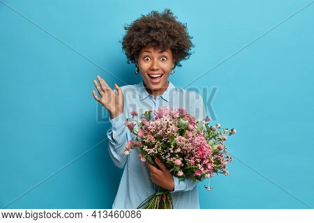Happy Womens Day Concept. Overjoyed Curly Haired Young Woman Raises Palm Feels Very Glad Raises Palm