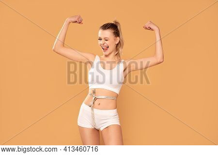 Smiling Slim Woman Measuring Her Waist With Tape .fit Young Lady In Perfect Shape, Happy With Her Bo